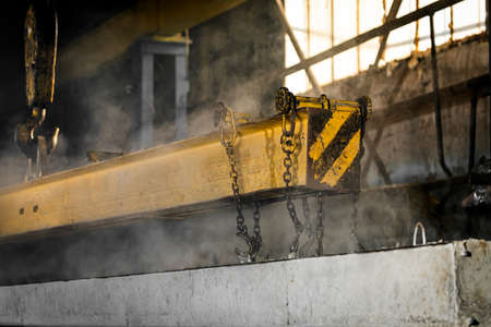 The production process is the creation of reinforced concrete pillars. Reinforced concrete pillars fixed with metal hooks and chains on the background of the plant