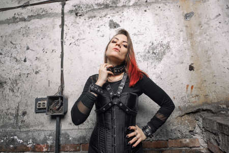 A attractive dominant woman with piercings and bright hair in a black corset, with leather harnesses and bracelets posing against the background of an old wall. Фото со стока