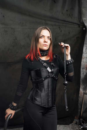 Beautiful lady in outfit.Close-up fashionable portrait of a model in a black corset and with leather harnesses. Attractive woman in an attractive outfit with belts