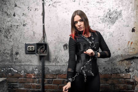 Sexy dominant woman with piercings and bright hair in a black corset, with leather harnesses and bracelets, hands tied with a leather bracelet, toys for adults, looks darkly, on an industrial background