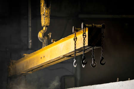 The crane moves a reinforced concrete product with holes. Reinforced concrete pillars fixed with metal hooks and chains on the background of the plant