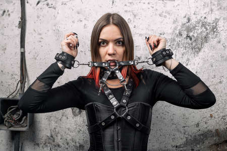 A attractive dominant woman with piercings and bright hair in a black corset, with leather harnesses and bracelets posing against the background of an old wall.