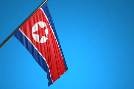 3D illustration of the national flag of North Korea on a metal flagpole fluttering against the blue sky.Country symbol.