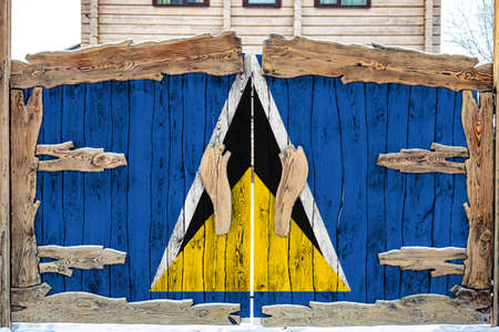Close-up of the national flag of Saint Lucia on a wooden gate at the entrance to the closed territory. The concept of storage of goods, entry to a closed area.