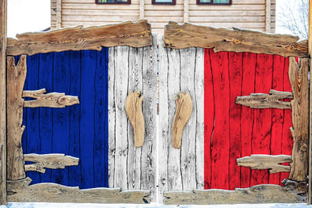 Close-up of the national flag of France on a wooden gate at the entrance to the closed territory. The concept of storage of goods, entry to a closed area.