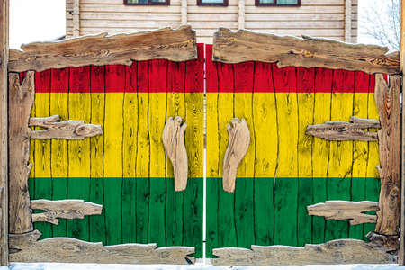 Close-up of the national flag of Bolivia on a wooden gate at the entrance to the closed territory. The concept of storage of goods, entry to a closed area.