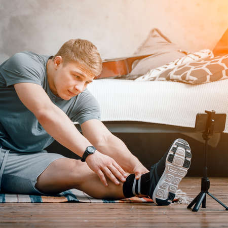 The strong man goes in for sports at home. Cheerful sporty man with blond hair stretches to the leg and watching video, shootting blog in the bedroom 免版税图像