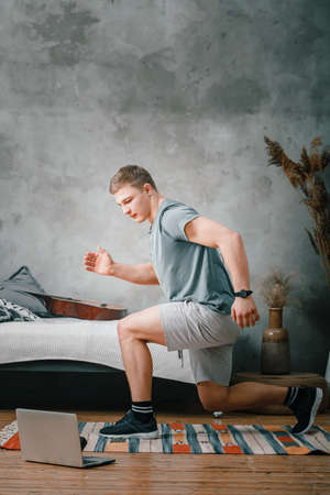 A cheerful athlete with blond hair lunges in the bedroom, next to a laptop with online training. The young man goes in for sports at home.