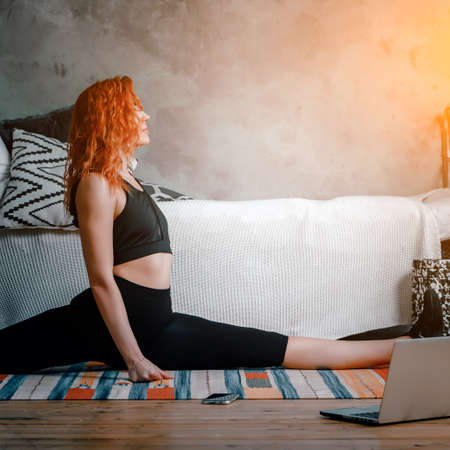 A young woman goes in for sports at home, online workout. The athlete stretching, meditating, sitting on a twine in the bedroom, in the background there is a bed, a vase, a carpet. 免版税图像
