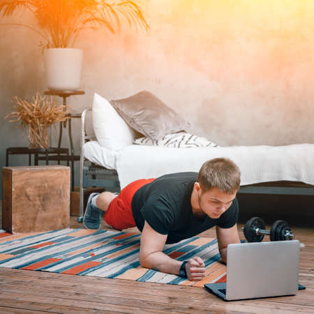 Young man goes in for sports at home, training online. The athlete makes a plank, watches a movie and studies from a laptop in the bedroom, in the background a bed, a vase, a carpet. 免版税图像