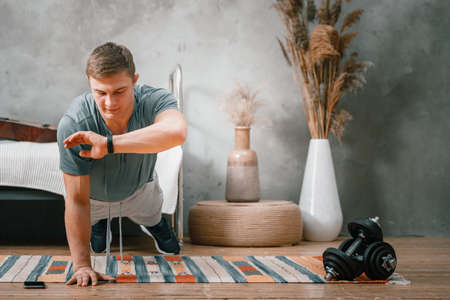 Young man goes in for sports at home, training online. The athlete makes a plank, looks at the time on a sports watch, a stopwatch in the bedroom, in the background a bed, a vase, a carpet.