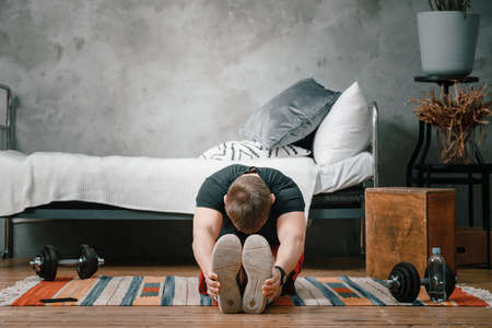 A young man goes in for sports at home, online workout from the phone. The athlete stretching in the bedroom, in the background there is a bed, a vase, a carpet. 免版税图像