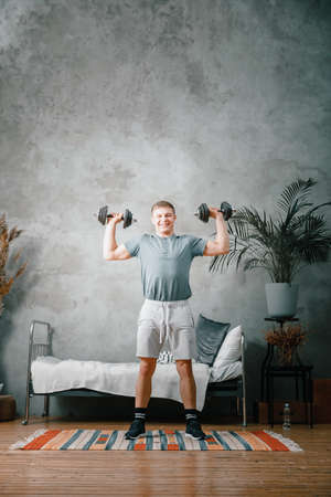 A athlete with blond hair shakes biceps in dumbbells in the bedroom, online training. The young man goes in for sports at home.