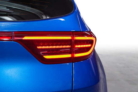 The back of a blue expensive crossover car: bumper, trunk lid, taillight on the back white background. Mock up for the advertising industry. New car concept
