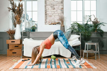 Beautiful young woman exercising in the bedroom, downward facing dog pose. Posture of the sun salutation