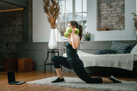 A cheerful athlete with black hair lunges in the bedroom with online training. The young woman goes in for sports at home.