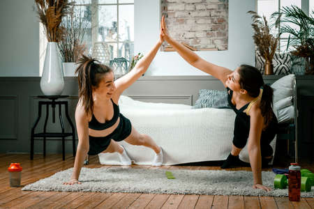 Two women friends at home chatting, smiling and makes training in bedroom. Two women girlfriends are stretching, look at each other, give five