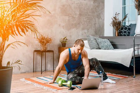 Close-up of a young man in a sports uniform is resting, stretching on the floor at home, watches a movie and studies from a laptop, a social network. Student loafing around