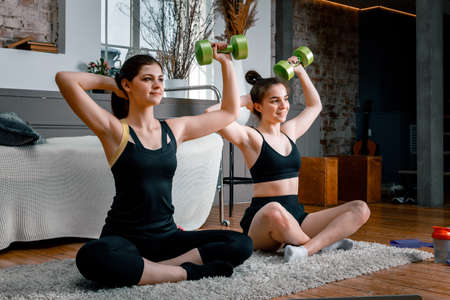 Young women go in for sports at home, workout online. Athletic woman doing hand biceps exercise with dumbbells in the bedroom
