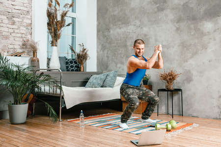 A young man goes in for sports at home, online workout from the laptop. The athlete makes squat, watches a movie in the bedroom, in the background there is a bed, a vase, a carpet. Фото со стока