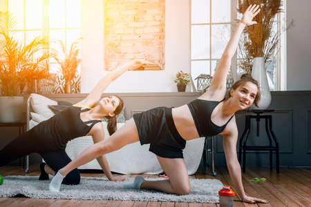 Young women goes in for sports at home, training online. Home workout with a friend, young woman do morning exercises, stretch to the side on the floor