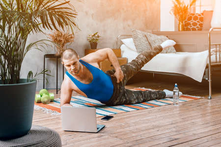 The young man goes in for sports at home. Cheerful sportsman with black hair shakes leg, lunges and watching online workout from laptop in bedroom