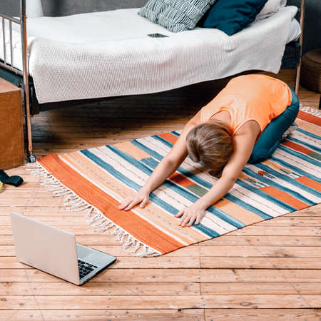 The young woman goes in for sports at home. Cheerful sportswoman with blond hair resting, stretchong on the floor at home in the bedroom