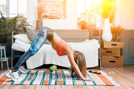 Beautiful woman do exercise in bedroom, yoga in everyday life. downward facing dog pose, adho mukha svanasana Фото со стока