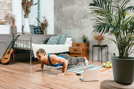 The young man goes in for sports at home. Sportsman with black hair does push-ups and watch movie, watching a workout online on carpet in bedroom Фото со стока