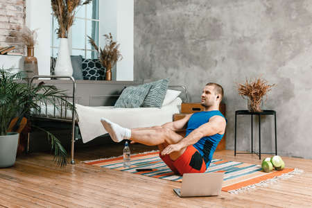 Young man goes in for sports at home, training online. The athlete makes the press, lifting his legs up, watches a movie and social networks on laptop