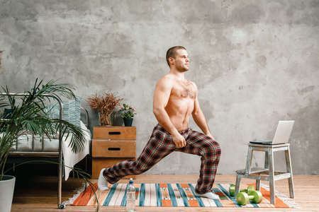 The young man goes in for sports at home. Sportsman with black hair in home pajamas does morning exercises, lunges on carpet in bedroom