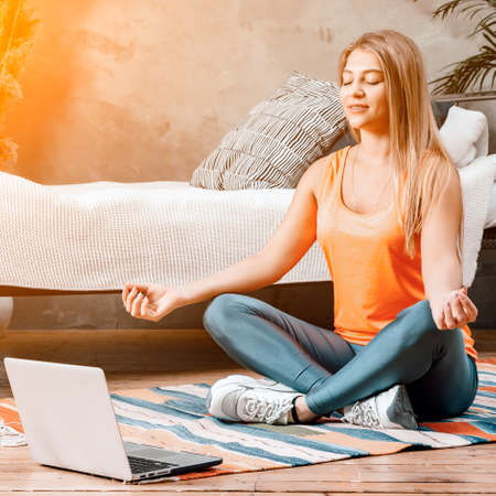 The young woman goes in for sports at home. Cheerful sportswoman with blond hair meditates in lotus position, resting on the floor at home in the bedroom