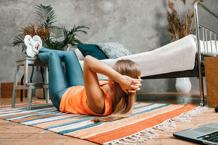 Young woman goes in for sports at home, training online. The athlete makes the press, lifting his legs up in bedroom