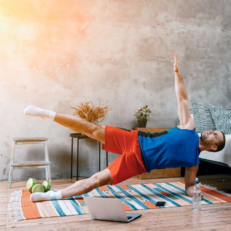 The young man goes in for sports at home. Cheerful sportsman with black hair does morning warm-up, pulls an arm and a leg to the ceiling, online workout from laptop in bedroom