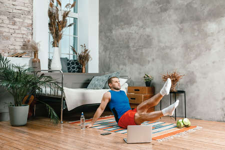 The young man goes in for sports at home. Cheerful sportsman with black hair makes press, lifting his legs up in the bedroom, next to there is a laptop with online training