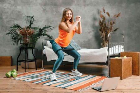 Young woman goes in for sports at home, training online. The athlete makes squat with sport fitness rubber bands, watch movie on laptop on background bed, vase, carpet Фото со стока