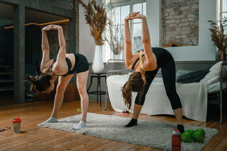 Young women goes in for sports at home, training online. Home workout with a friend, two young women bend forward, hands behind the head at home Фото со стока