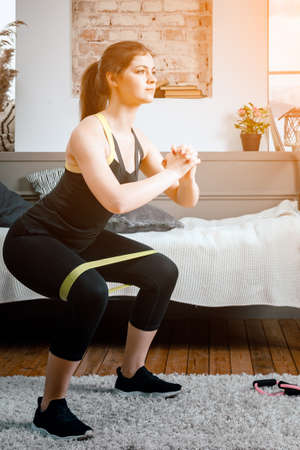 Positive athletic woman with neatly tied hair and tight sportswear doing squats with sports fitness bands at home. The young woman goes in for sports at home.