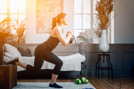 Positive athletic woman with neatly tied hair and tight sportswear lunges with box at home. The young woman goes in for sports at home. Standard-Bild