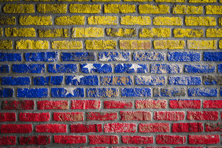 National flag of Venezuela depicting in paint colors on an old brick wall. Flag banner on brick wall background.