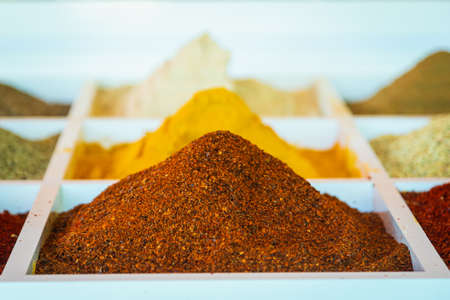 Close-up of beautiful rows of fresh spices: turmeric, cumin, red and black pepper, parsley, peppers, greens. Various spices on the market showcase