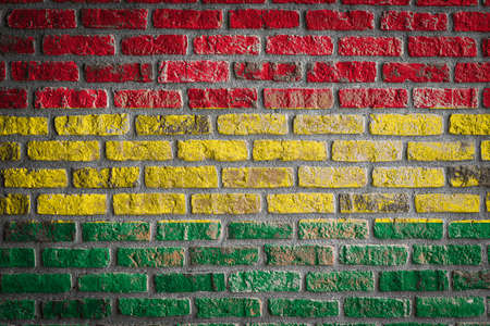 National flag of Bolivia depicting in paint colors on an old brick wall. Flag banner on brick wall background.