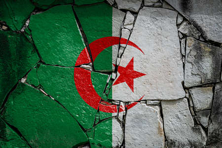 National flag of Algeria depicting in paint colors on an old stone wall. Flag banner on broken wall background. Archivio Fotografico