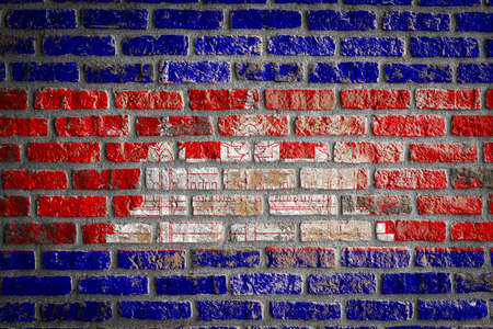 National flag of Cambodia depicting in paint colors on an old brick wall. Flag banner on brick wall background.