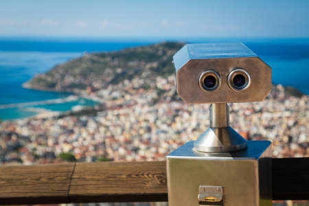 Close-up metal binoculars for public use with views of the beautiful antique city, port and sea