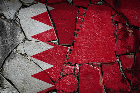 National flag of Bahrain depicting in paint colors on an old stone wall. Flag banner on broken wall background. Archivio Fotografico