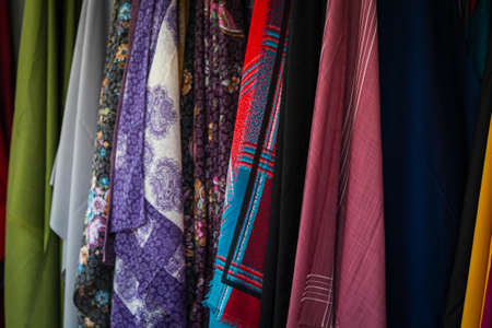Close-up rows of pieces of fabric made of cotton, polyester, tapestry and other materials of different colors and prints for sewing curtains, handkerchiefs and clothing