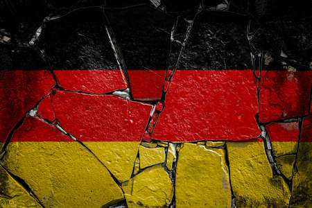 National flag of Germany depicting in paint colors on an old stone wall. Flag banner on broken wall background.