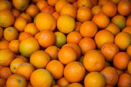 Oranges background. Fresh oranges variety grown in the shop. Oranges suitable for juice, strudel, Orange puree, compote