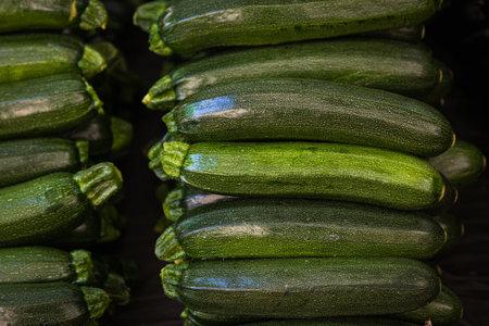 Fresh organic green zucchini on a fresh market, background. Zucchini texture. Lots of organic vegetables